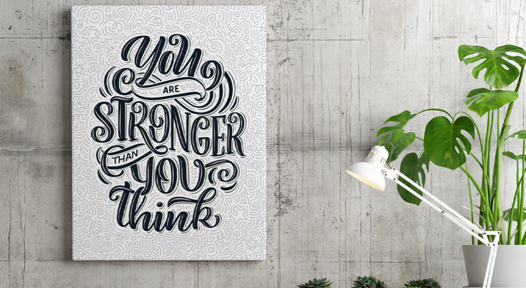 """A canvas print features typographic art with the quote """"You are stronger than you think"""" styled in black, grey and white above what appears to be a workstation with a lamp and a houseplant."""