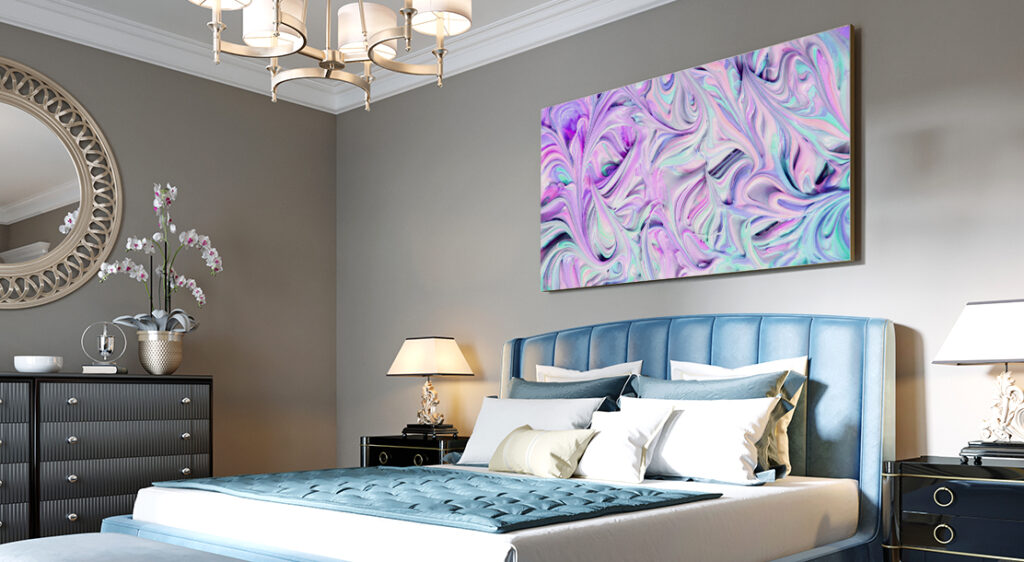 A large, oversized canvas print of abstract purple, blue and white swirls hangs above a bed in a large bedroom with grey walls.