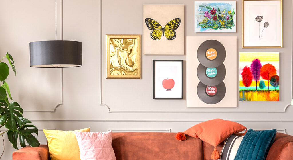 Cropped image of a living room wall, above a dark orange couch features an eclectic gallery wall of a butterfly canvas print, a collection of record albums printed on canvas, along with some framed prints of flowers, an apple, trees, and abstract swirls. the canvas and framed prints of different sizes are grouped closely together on the wall.