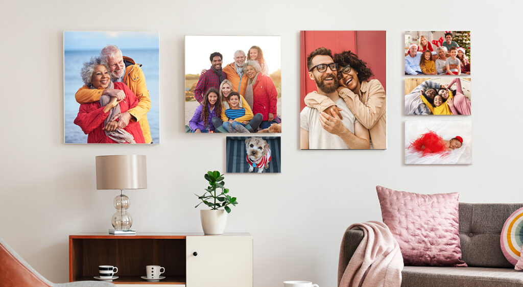 A living room wall displays a collection of family photos  printed on canvas in varying sizes. Featured on a white wall, the canvas prints showcase a portrait of grandparents, a young couple, a large family group photo, a brand new infant, and a photo of the family dog.