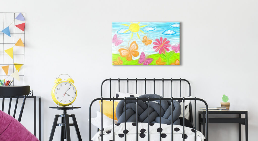 A medium sized canvas print of a child's drawing hangs above a small twin bed in a child's bedroom. The child's drawing is a bright landscape of green grass, blue sky and a bright yellow sun with large butterflies and a flower in the foreground.