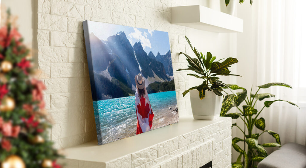 A canvas print photo leans on top of a white brick fireplace mantle beside large houseplants. The canvas is a photograph of an unknown glacier lake in Banff and centered in the image is a woman looking at the mountains beyond the lake with her back to the viewer, wrapped in a Canadian flag. The edge of a Christmas tree peeks out from the edge of the living room.