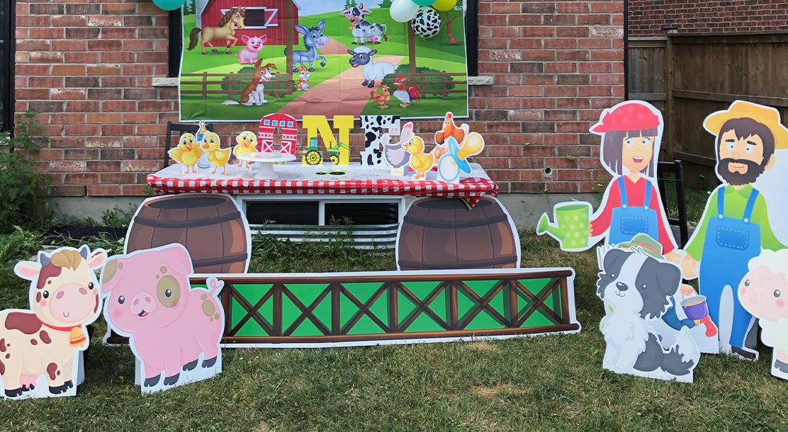 """Photo of a children's party, with a farm theme. Cardboard cutouts of barnyard animals are in the foreground, and a table is made to resemble a barn. On the table is a cutout saying """"ONE"""". Behind the table is another poster depicting a farm scene."""