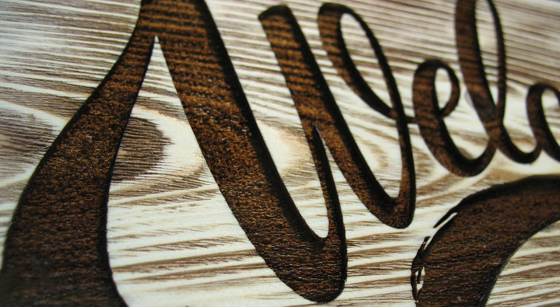 Detail of a laser-engraved wooden welcome sign.