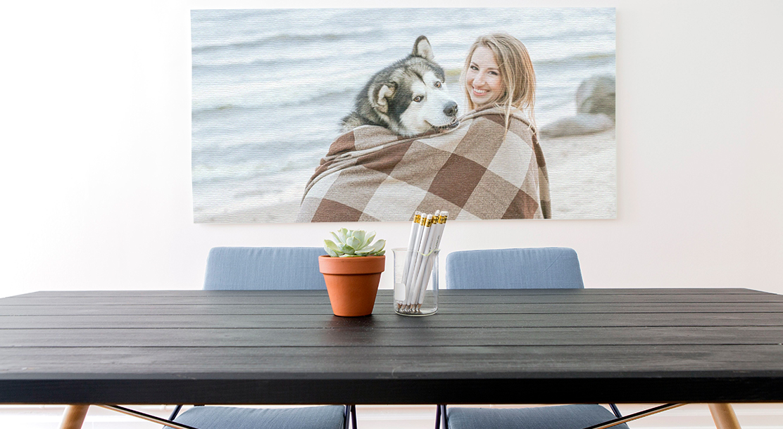 Image of a wall-mounted print of a woman and her dog, hung over a table and desk space.