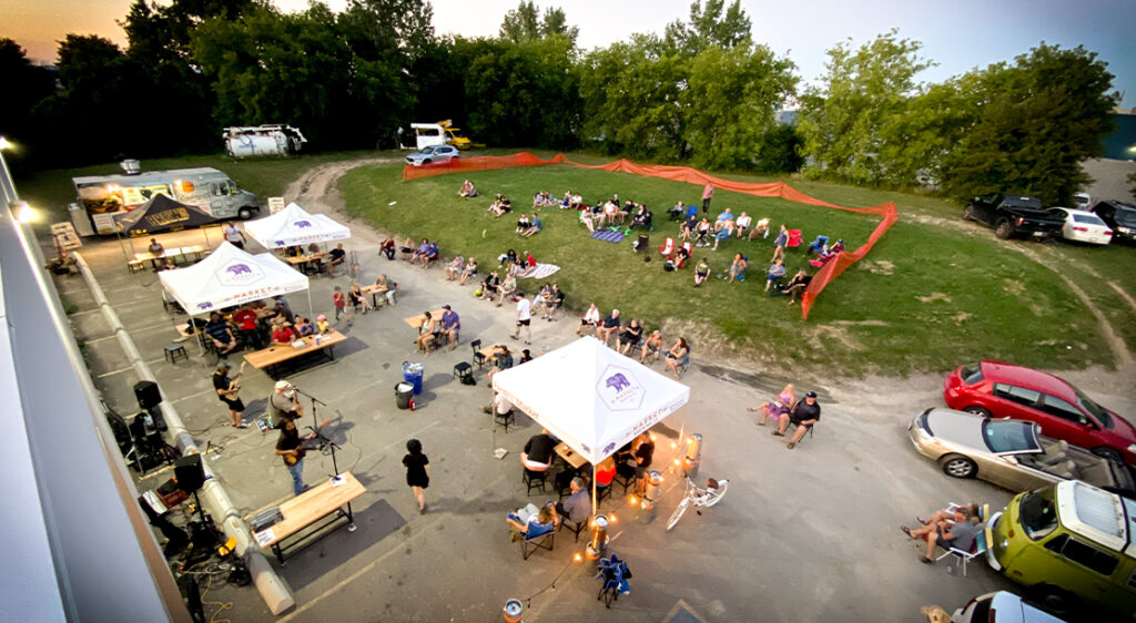 Birds eye view or drone image that shows the Market Brewing patio. Half parking lot and half grassy hill, customers enjoy the atmosphere under pop-up tents with picnic tables and lawn chairs on a summer evening.