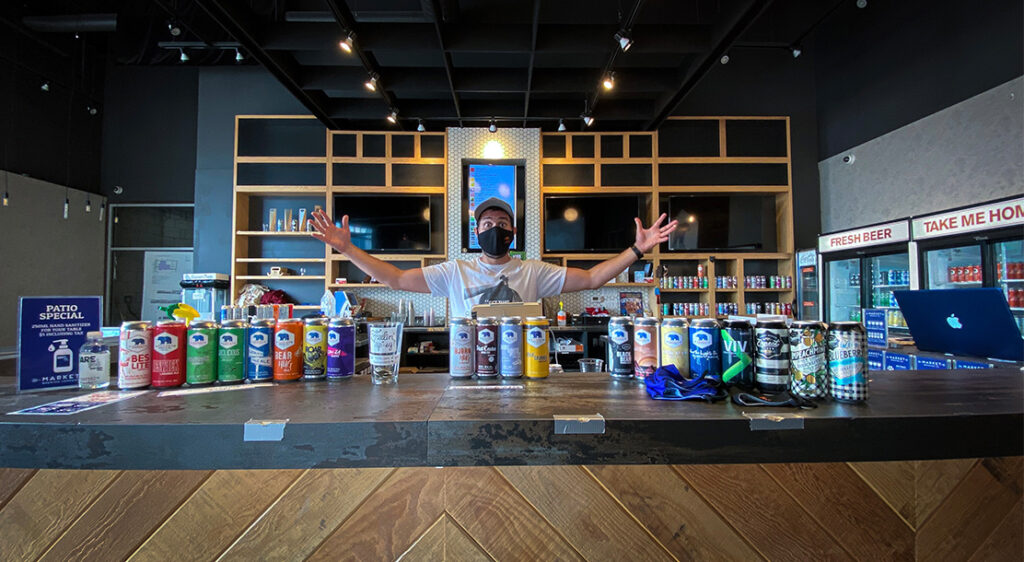 Masked bartender in baseball cap stands behind bar top with his arms spread wide showing off a display of the Market Brewing beer cans and bottle shop brews lined up side by side.