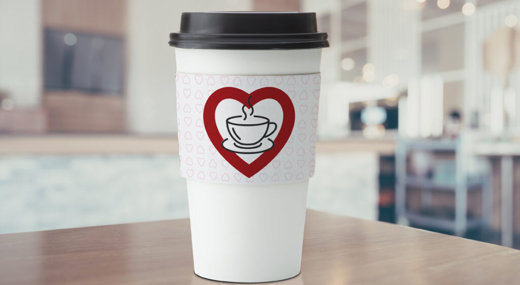 Close up of generic take-out coffee cup and lid, with a cardboard cup sleeve that has coffee shop logo and hearts behind it. The cup sleeve has been designed just for Valentine's day.