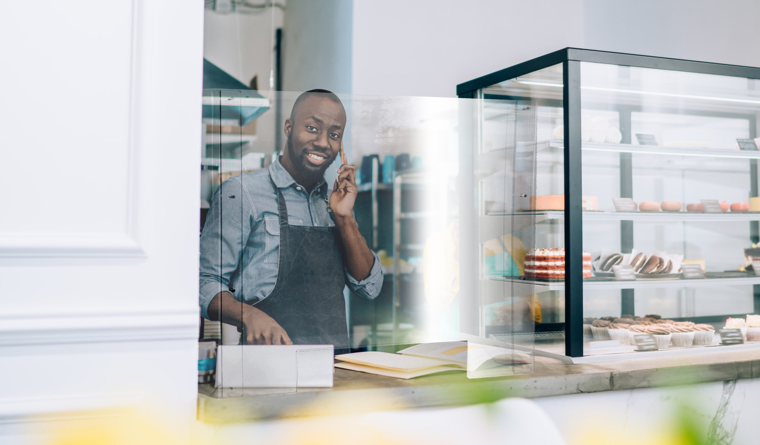 Image of a man behind a bakery countertop, smiling with a cellphone. He is behind a countertop plastic shield.