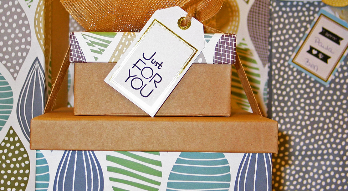"""Photo of several gift wrapped boxes in various patterns. The centermost box has a large tag saying """"just for you""""."""