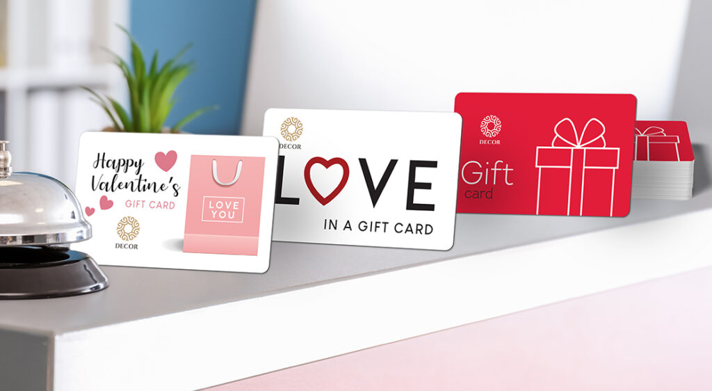 Three Valentine's Day themed plastic gift cards are propped up on a retail counter top to be displayed.