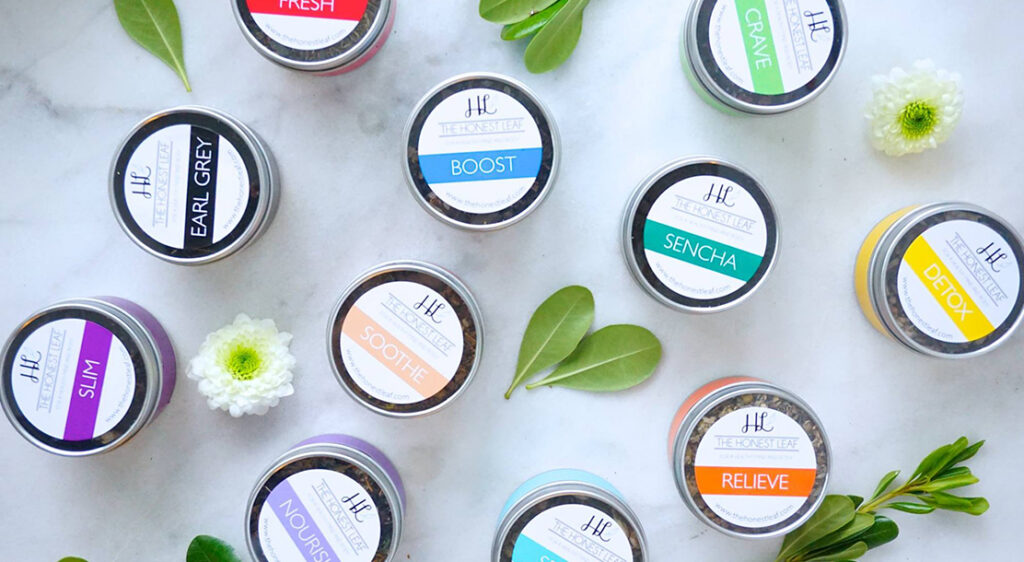 Photograph of round tea tins scattered on a white-marble counter top with colourful labels of the tea names of Honest Leaf blends as follows Earl Grey, Slim, Sencha, Boost, Sooth, Nourish, Relieve, Detox, and Crave.