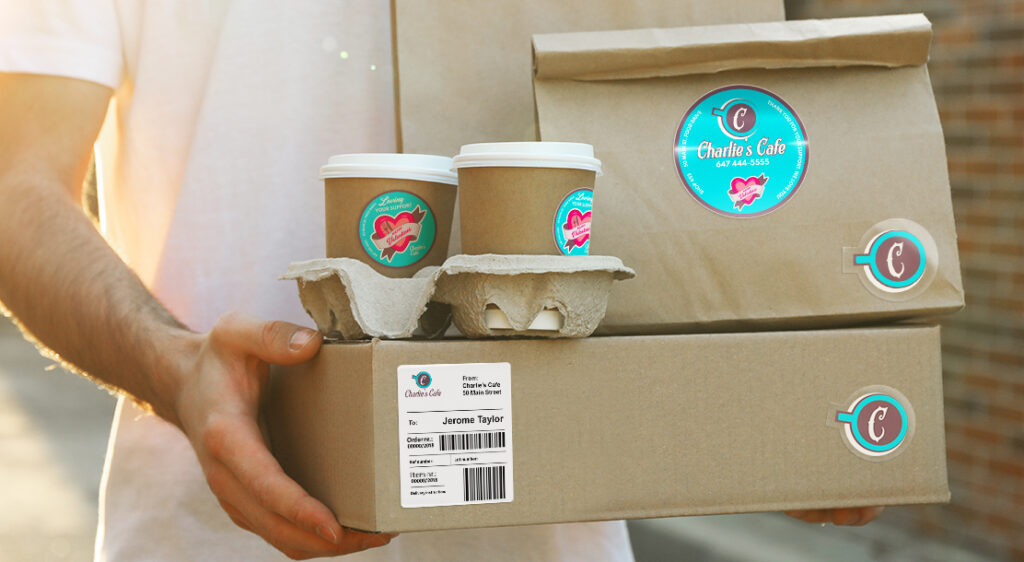 A close-up image of a man carrying a package delivered by mail. On top of this package, a brown paper bag and a tray of coffee cups are balanced. The package, the bag and the cups all have a branded label attached with Valentine's day hearts.