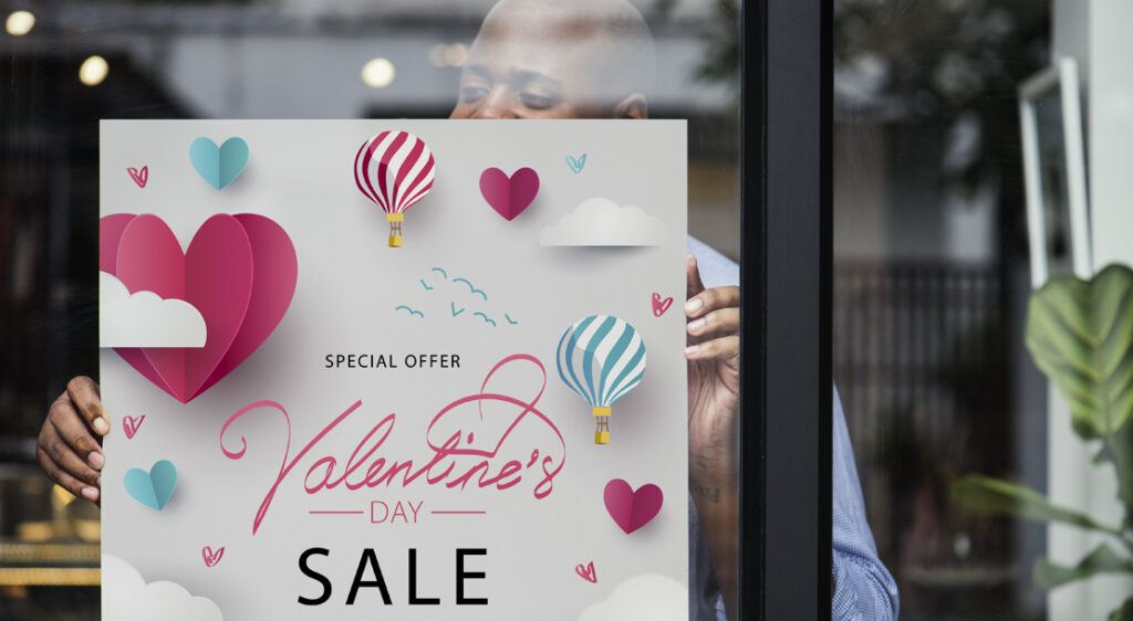 Black store owner hangs a seasonal Valentine's day poster in a storefront window that advertises a sale.