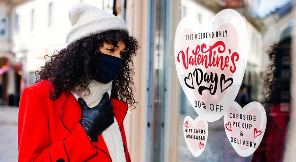 Bundled and masked woman on sidewalk of downtown district is looking at vinyl stick-on window decals in a retail storefront that advertise curbside pickup+ delivery, Valentine's Day sales, and gift card availability.